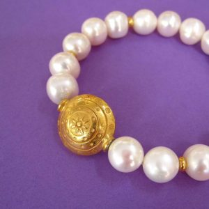 Weißes Perlenarmband mit großem vergoldeten Ornament